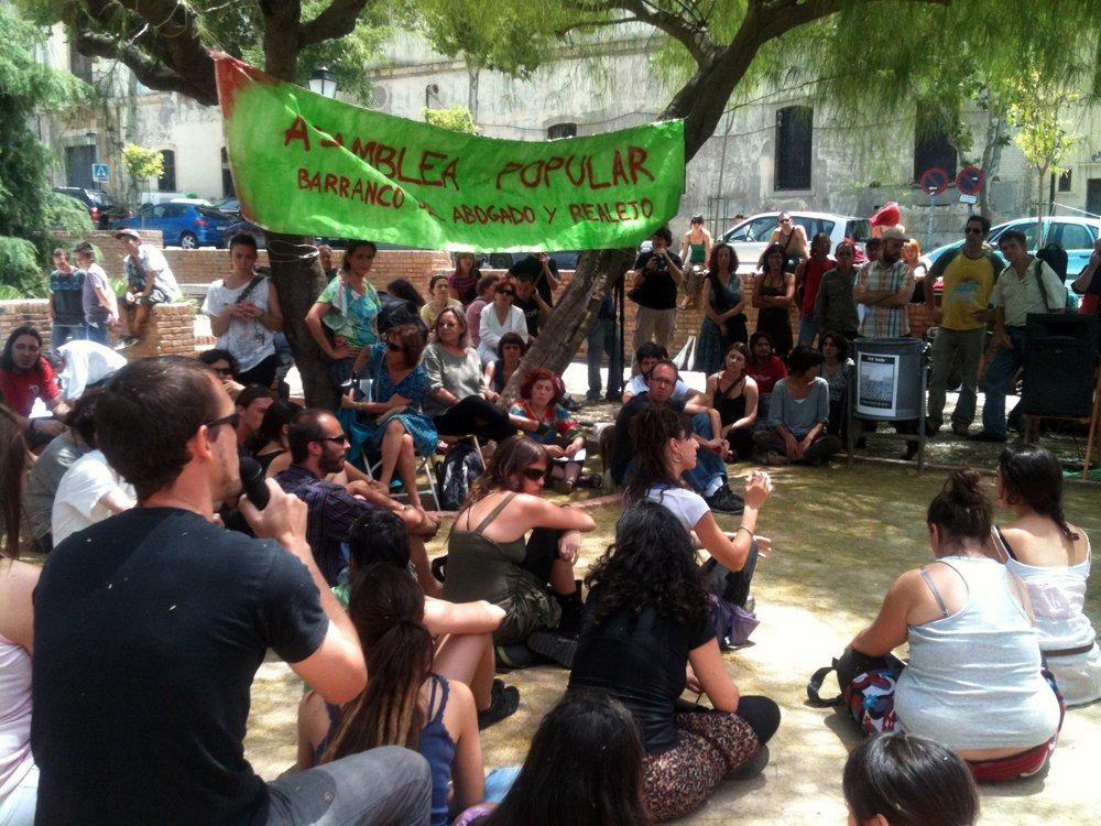 Un participante habla para para la asamblea de 'indignados' en el Campo del Príncipe