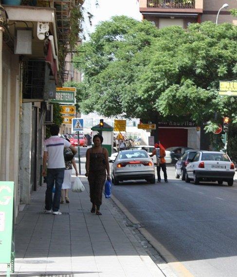 Una inmigrante pasea por una calle de la Chana