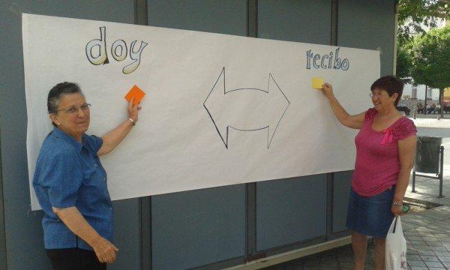 Dolores (izquierda) explica junto a otra vecina el funcionamiento del banco.