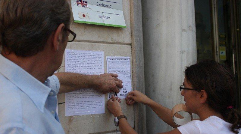 Activistas de Stop Desahucios pegan octavillas reivindicativas.