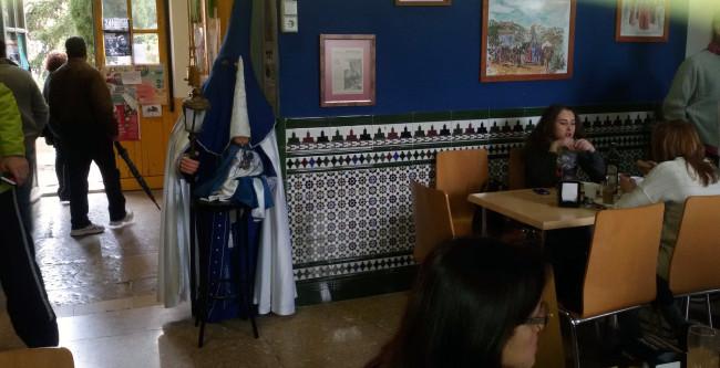 La figura de dos penitentes, uno vestido de niño, a la entrada de la cafetería de Odontología.